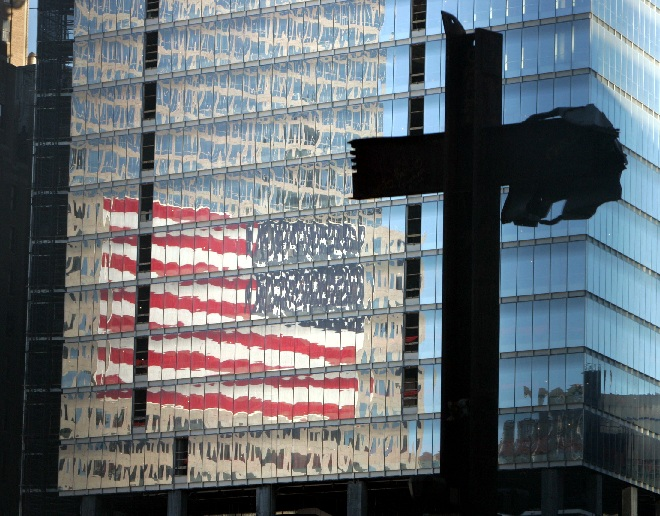 Girders in the shape of a cross, preserved from the wreckage of the World Trade Center (WTC), stand over the WTC site in New York September 10, 2004. New York City plans to mark the third anniversary of the attacks on the trade center with an observance at the site on September 11 with parents and grandparents of victims reading their names. The American flag is reflected on the surface of the new 7 World Trade Center Building, under construction, at rear. The original 7 World Trade Center, which stood at the same location, burned and collapsed in the attack three years ago.
